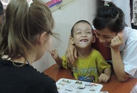 A Speech Therapy volunteer works on a language task with a disabled boy at our internship in Vietnam.