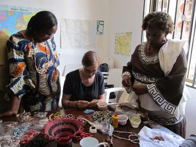 Projects Abroad volunteer in Micro finance makes beads with Tanzanian women