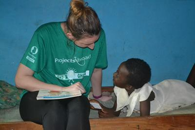 Projects Abroad Social Work intern talks with a Ghanaian child in Ghana, Africa.