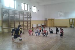 A Soccer volunteer leads a sports team in Romania through a stretching routine before they start their practice.
