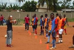 A volunteer works with a local soccer team in Togo, leading them through a drill to improve their ball skills and technique.
