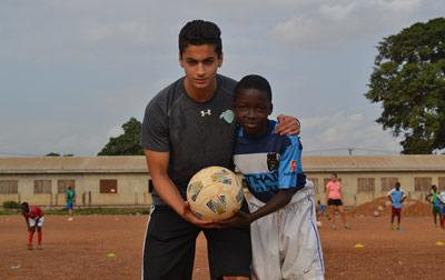 Projects Abroad Sports volunteer poses with a boy at a local football club in Ghana