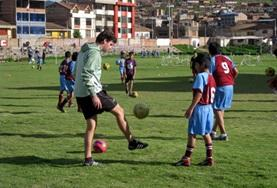 A Sports volunteer teaches school children his technique for kicking a soccer on our Multi-sports project in Peru.