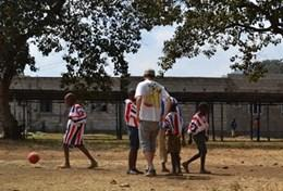 A volunteer coaches a group of students during a school sports lesson in Tanzania.